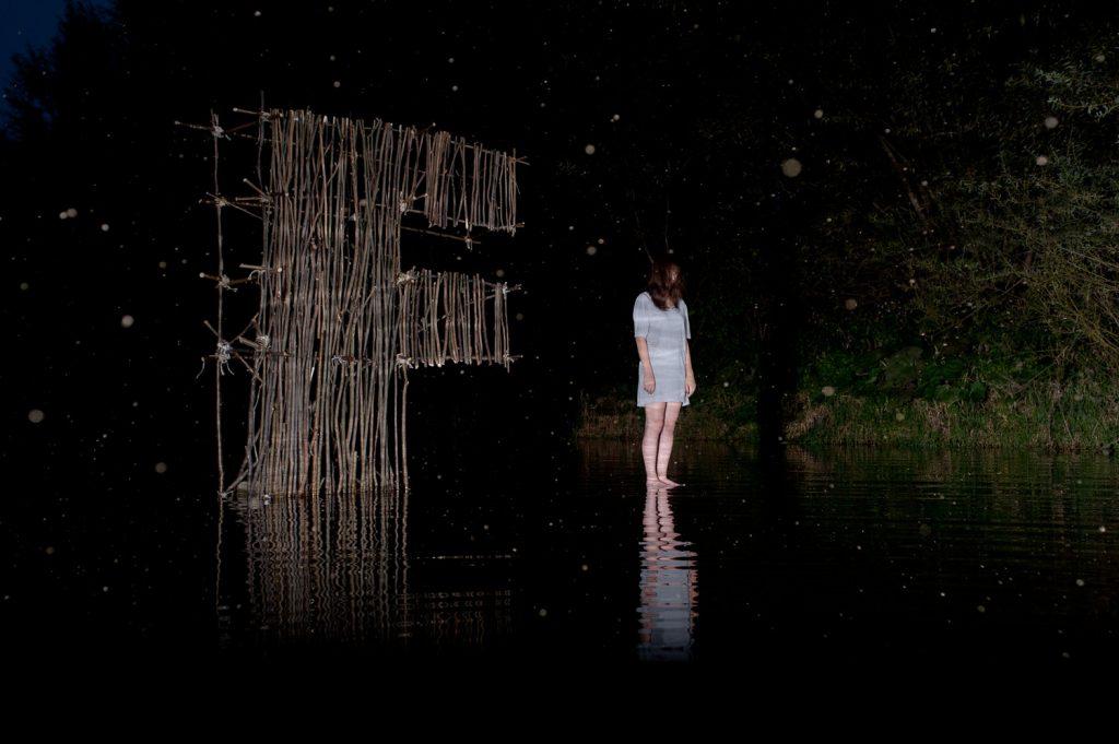 Litera F nocą, przed nią postać zjawy (inna perspektywa)