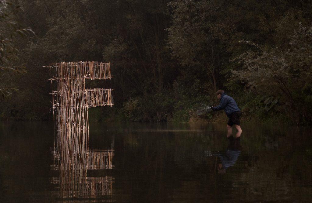 Postać skrada się w kierunku litery na rzece oświetlając ją latarką (inna perspektywa)